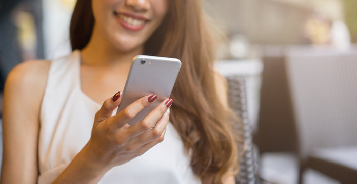 close up young beautiful asian woman looking at  smartphone for video online chat with friends   or surf the internet or playing mobile application in relax time, millennial  lifestyle concept
