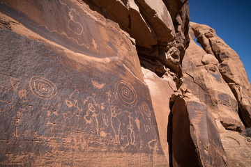 Native American petroglyphs etched onto sandstone rock wall below arch