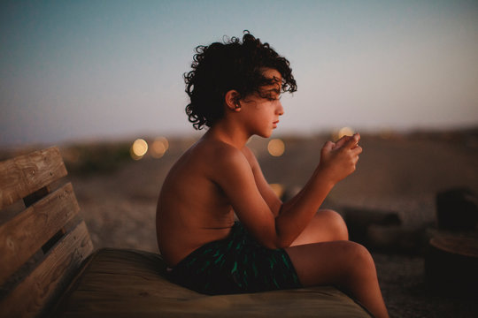 A young boy playing with his smartphone  in desert during sunset
