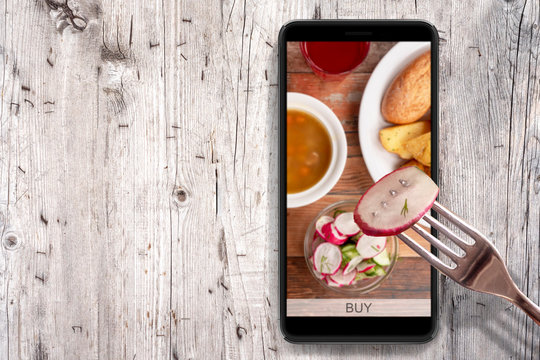 Order and food delivery from your smartphone. Smartphone on wooden background