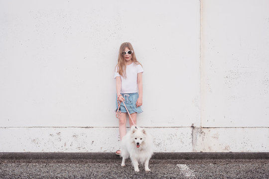 Young girl holding onto a white fluffy dog outside
