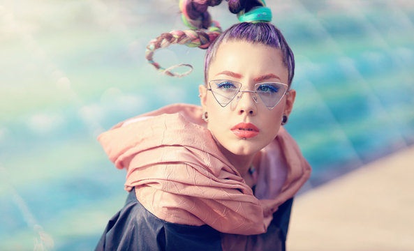The avant-garde portrait girl with unusual make up and fancy sun glass. Portrait of young woman chilling in the sun. Woman with avant-garde hair and bright make-up. Fashionable urban toning