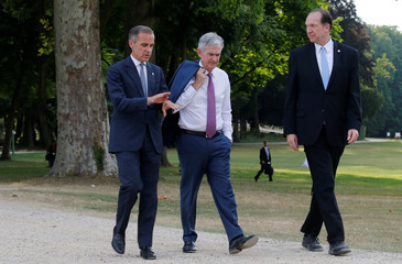 Bank of England governor Mark Carney, Federal Reserve Board Chairman Jerome Powell and World Bank President David Malpass walk in the garden before posing for a family photo during the G7 finance ministers and central bank governors meeting in Chantilly