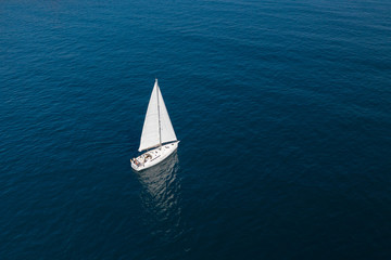 white sailing yacht in the blue sea top view