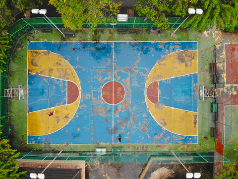 Aerial view of basketball court with players in public park in Bangkok. Top view of basketball court