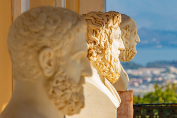 A row of three marble busts of men in the Sissi Palace near Gastouri on Corfu, Greece