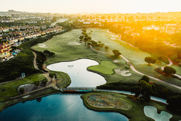 Aerial view of houses and golf course with artificial lake