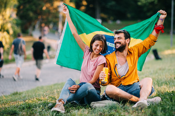 Young couple dancing at a festival in the park with a Brazil flag