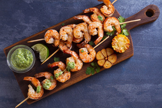 Cilantro lime grilled shrimps. Shrimps on skewers with garlic butter sauce. View from above, top studio shot