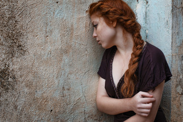portrait of a sad red-haired girl, sadness and melancholy in her eyes Wall mural