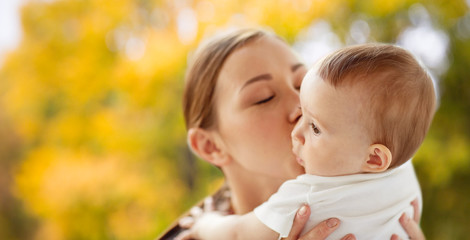 family, child and parenthood concept - close up of happy smiling young mother kissing little baby over autumn background