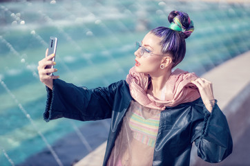 Portrait of a young lady with crazy look taking self-portraits (selfie). Urban outdoor with fountains in background. Model girl wearing stylish sunglasses, avangarde hairstyle and make-up