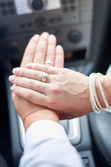 Newlyweds in the car show hands with wedding rings on the fingers.