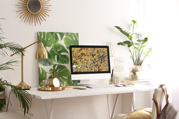 Modern workplace with computer and golden decor on desk near wall. Stylish interior design