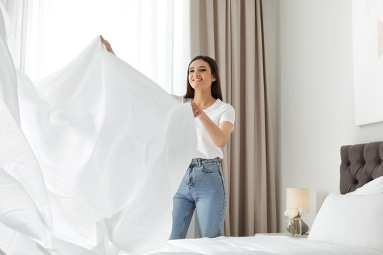 Happy young woman with clean bedsheet in room. Laundry day