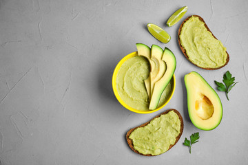 Flat lay composition with bowl of guacamole made of ripe avocados on grey table. Space for text