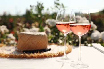 Glasses of rose wine and straw hat on white wooden table outdoors. Space for text