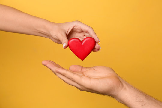 Woman giving red heart to man on yellow background, closeup. Donation concept