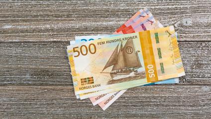 Norwegian kroner bills stacked on wood table