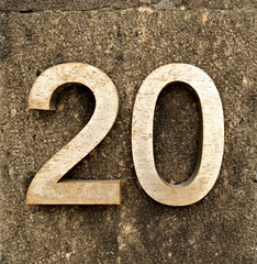 20, number twenty, metal digits on stone background.