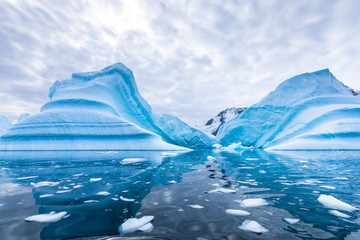 Iceberg in Antarctica floating in the sea, frozen landscape with massive pieces of ice reflecting...