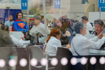 Volunteer Chris Perry dressed in a Superman costume, watches over attendees as they arrive at the pop culture festival Comic Con International in San Diego, California