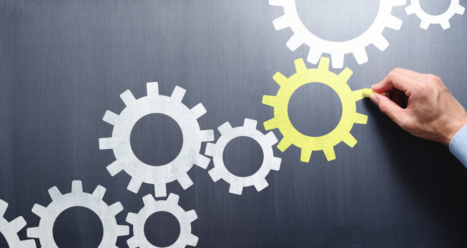 Business process management and solution. Businessman drawing connecting gears on chalkboard.