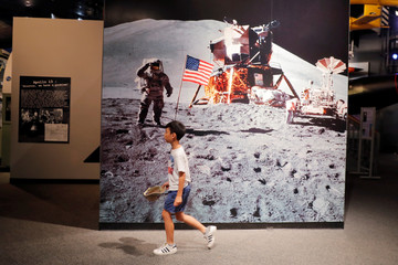 A young boy walks past a photograph of Buzz Aldrin on the surface of the moon during the Apollo 11 mission at the Cradle of Aviation Museum in Garden City, New York