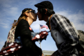 A flag of the U.S. flutters behind a Mexican couple kissing before crossing into El Paso, Texas, U.S. on the Paso del Norte international bridge, in this picture taken from Ciudad Juarez