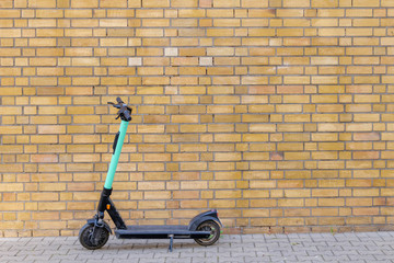 One parking E-scooters, Eco friendly mobility concept of sharing transportation with Electric Scooter, on sidewalk in front of yellow brick vintage wall in old town.