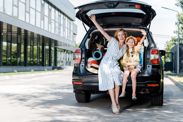 happy mother and daughter with outstretched hands near car