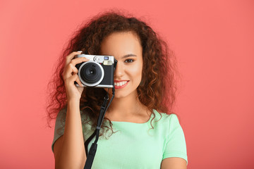 Beautiful young woman with photo camera on color background