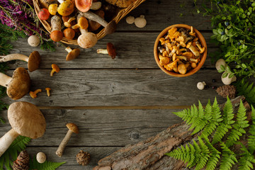 Mushrooms on old wooden background. Card on autumn or summertime. Forest harvest. Boletus, chanterelles, leaves, berries. Flat lay. Fototapete