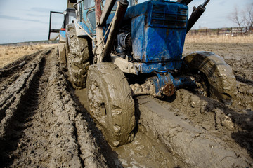 Tractor stuck in the mud on a bad road. Clay stuck on wheels. Wall mural