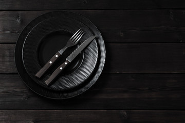 black plates on wooden background