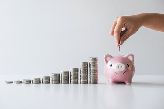 Hand putting coin into piggy bank for planning step up growing and savings