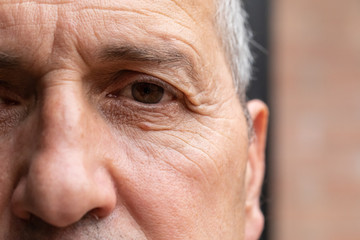 An extreme closeup and front view on the eye and face of an older gentleman. Details of the crow's feet and wrinkles of a man in his fifties.