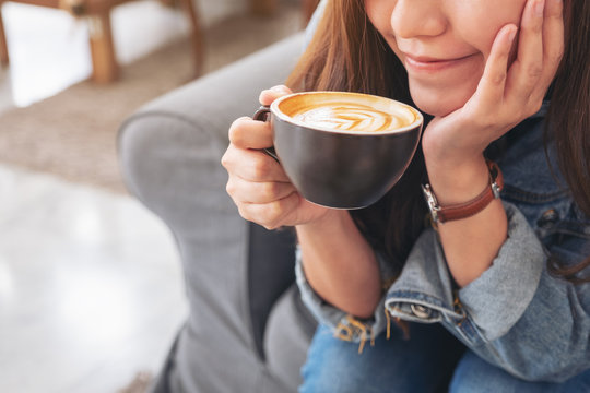 Closeup image of a beautiful asian woman holding and drinking hot coffee in cafe