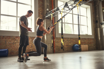 Postive workout. Beautiful young woman in sportswear doing trx exercises at gym while her personal...