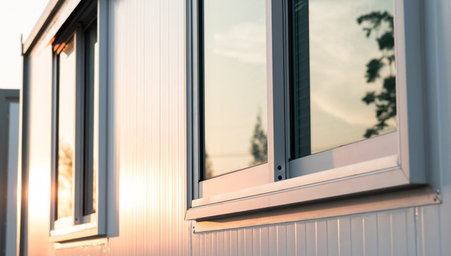 beautiful warm sunrise light shining on house glass window with town nature reflection in the morning, modern home exterior view