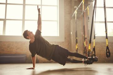 Making perfect body. Young athletic man exercising with suspension straps at gym