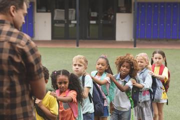 School kids standing in a queue in the schoolyard