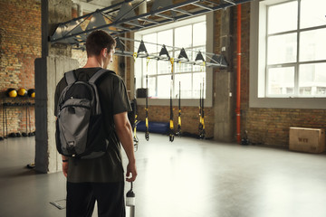 Morning workout. Back view of young man with backpack standing in empty gym