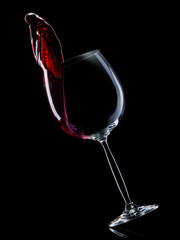 Glass for red wine with splashes isolated on black background.