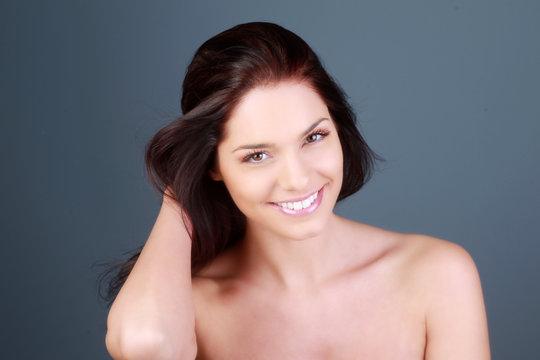 Portrait d'une jeune femme brune souriante en studio