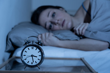 Attractive woman in bed staring at alarm clock trying to sleep feeling stressed and sleepless Wall mural