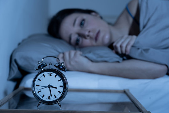 Attractive woman in bed staring at alarm clock trying to sleep feeling stressed and sleepless