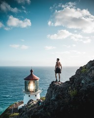 Shirtless fit male standing on a rocky cliff near a lighthouse beacon and the sea