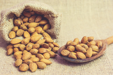 Ripe unpeeled almonds in jute bag and on wooden spoon on jute background