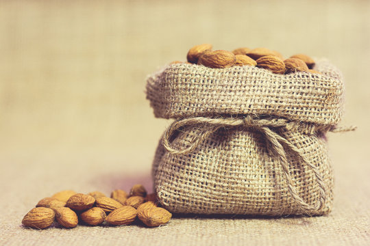 Ripe unpeeled almonds in jute bag on jute background. Food photography. Minimalist photography.